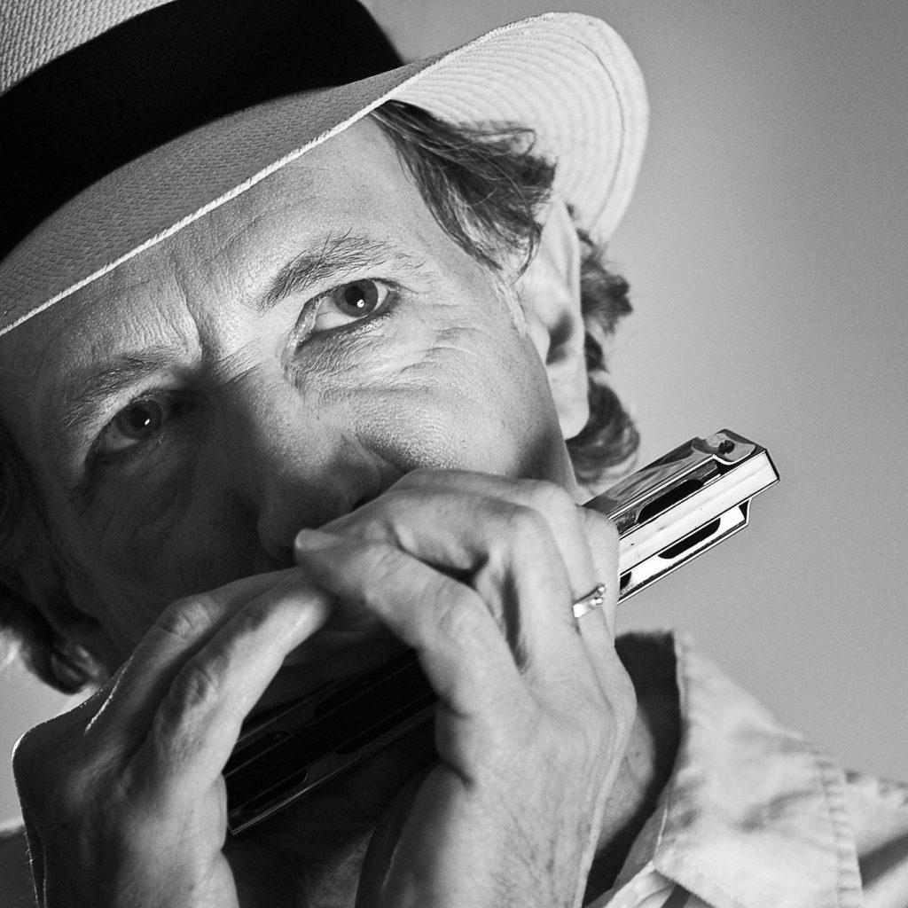 Jay Sewall joue de l'harmonica.